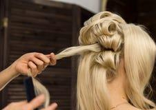 De kapper doet kapsel voor luxueuze blonde vrouw kapsel in de vorm van grote krul Het kapsel van het conceptenhuwelijk stock afbeeldingen