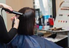 De kapper doet richt het haar op haarijzer aan een jong meisje stock fotografie