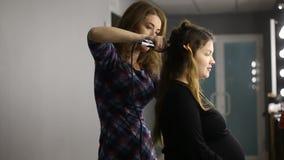 De kapper doet richt het haar op haarijzer aan een jong meisje, brunette in een schoonheidssalon Professionele haarverzorging stock videobeelden