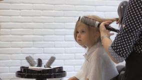 De kapper droogt de droogkap een klein meisje Haarverzorging in de schoonheidssalon stock videobeelden