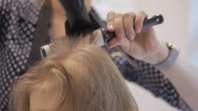 De kapper droogt de droogkap een klein meisje Haarverzorging in de schoonheidssalon stock footage