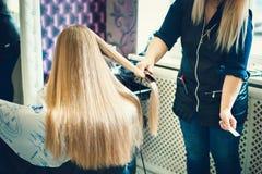 De kapper droogt en kamt een lang eerlijk haar Vector illusration van meisje met lang haar stock fotografie