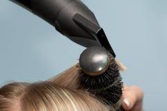 De kapper droogt het haar in een schoonheidssalon stock foto