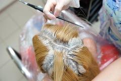 De kapper gebruikt een borstel om de kleurstof op het haar, voor D toe te passen royalty-vrije stock foto's