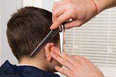 De kapper houdt een kam en een schaar in haar hand en maakt een kapsel voor de donker-haired jongen royalty-vrije stock foto's