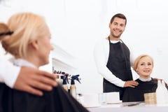De kapper kiest kapsel voor rijpe aantrekkelijke vrouw in schoonheidssalon royalty-vrije stock fotografie