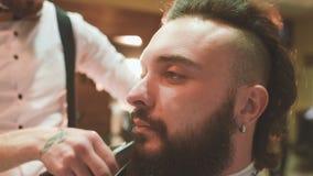 De kapper maakt de besnoeiing of het stileren van een baard stock videobeelden