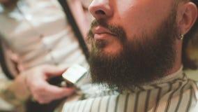 De kapper maakt de besnoeiing of het stileren van een baard stock video