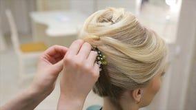De kapper maakt een decoratie aan het haar van een jonge blonde haired vrouw, close-up vast stock videobeelden
