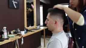 De kapper maakt een modieus kapsel voor een mannelijke cliënt stock videobeelden