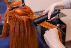De kapper maakt kapselmeisje met lang rood haar in een schoonheidssalon stock foto's