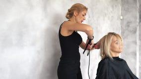 De kapper maakt krullen gebruikend een krullend ijzer stock video