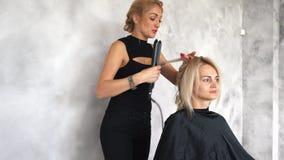 De kapper maakt krullen gebruikend een krullend ijzer stock videobeelden