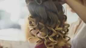 De kapper maakt krullen voor vrouw en de kunstenaar past make-up op gezicht toe stock footage