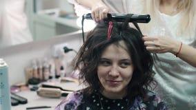 De kapper maakt tot een plechtig kapsel aan een positief cliëntmeisje stock footage