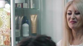 De kapper maakt tot een plechtig kapsel aan een positief cliëntmeisje stock video