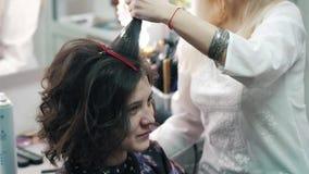 De kapper maakt tot een plechtig kapsel aan een positief cliëntmeisje stock videobeelden