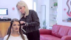De kapper maakt tot krullen aan jong mooi meisje stock footage