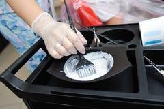 De kapper met een borstel neemt een verf van de schotels voor verf royalty-vrije stock afbeelding