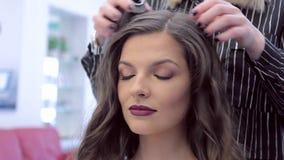 De kapper is met klaar het tot stand brengen van een modieus beeld van een jong mooi meisje stock video