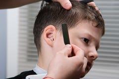 De kapper past haarstijl aan jongen aan royalty-vrije stock foto
