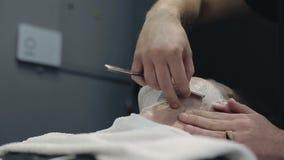 De kapper scheert de baard van de cliënt in de herenkapper stock videobeelden
