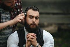 De kapper scheert een gebaarde mens stock fotografie
