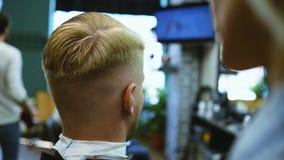 De kapper snijdt een gebaarde mens met schaar in de salon stock footage