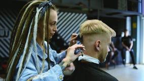 De kapper snijdt een gebaarde mens met schaar in de salon stock video