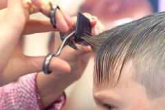 De kapper snijdt klappen met schaar op het hoofd van de jongen De handenclose-up van de stilist, zijaanzicht royalty-vrije stock afbeelding