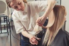 De kapper snijdt lang haar in haarsalon stock foto
