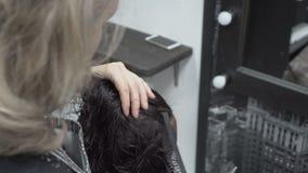 De kapper-stilist kamt en snijdt meisje van het schaar het natte haar dat in de Kapperswinkel voor de spiegel zit De zorg van het stock footage