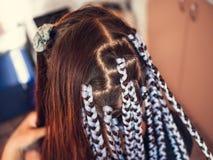De kapper weeft vlechten met kanekalonmateriaal aan jonge meisjes hoofd, dikke vlechten of vlechten - de vlechten van Afrikaan of royalty-vrije stock afbeelding