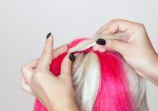 De kapper weeft vlechten met roze kanekalons mooi blonde stock afbeeldingen