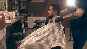 De kapper wordt klaar voor het werk De kapper omvat de cliënt met een kaap stock videobeelden