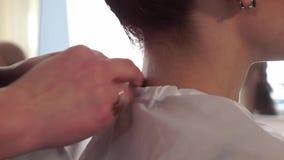 De kapper zet op de kaap op de vrouwelijke cliënt stock videobeelden