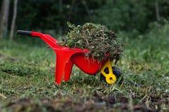 De kar van rode kinderen met gras en hooi het schoonmaken van het kind proces stock afbeelding