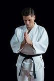 De karatespeler in gebed stelt stock afbeeldingen