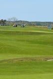 De karren en de spelers van het golf op cursus bij landclub royalty-vrije stock foto's