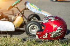 De Kartingscompetities, een rode beschermende helm ligt tegen de achtergrond van het rennen carting, close-up stock afbeeldingen