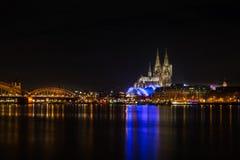 De Kathedraal van Keulen bij Nacht met de Rivier Rijn en de Hohenzollern-Brug Stock Afbeelding