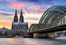De Kathedraal van Keulen en Hohenzollern-Brug bij zonsondergang - nacht stock foto