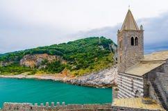 De katholieke kerk van Chiesasan pietro met klokketoren, Lord Byron Parque Natural-park, Palmaria-eiland met groene bomen, klippe royalty-vrije stock afbeeldingen