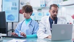 De Kaukasische arts en de jonge verpleegster werken bij hetzelfde bureau stock footage