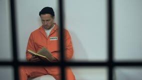 De Kaukasische bijbel van de gevangenelezing in cel, veroordeelde zondaar die aan godsdienst draaien stock footage