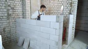 De Kaukasische bouwer in het werkslijtage het leggen blokkeert en het controleren van het met bellenniveau stock video