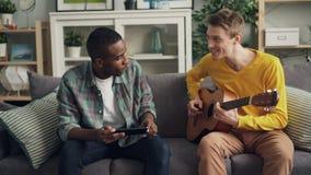 De Kaukasische jonge mens en zijn Afrikaanse Amerikaanse vriend leren om de gitaar te spelen samen gebruikend tablet het besteden stock footage