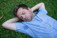 De Kaukasische, jonge mens rust op groen gras en kijkt op zijn nat overhemd royalty-vrije stock fotografie