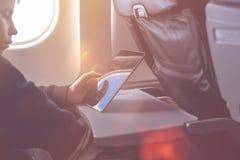 De Kaukasische jongen maakt veiligheidsgordel vast en het gebruiken van tabletpc en nemend beeld tijdens luchtvlucht stock foto's