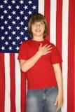 De Kaukasische jongen met overhandigt hart met Amerikaanse vlagachtergrond Royalty-vrije Stock Afbeeldingen